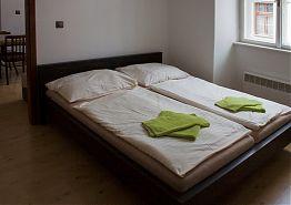 Manželská postel v ložnici apartmánu