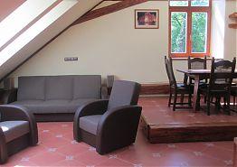 Obývací pokoj s jídelním stolem a sedačkou.