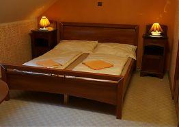 Manželská postel v dvojlůžkovém pokoji v apartmánu Terasa.