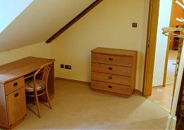 Stůl a úložný prostor v pokoji.
